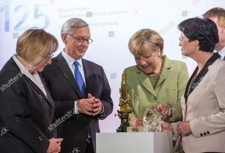 German Chancellor Angela Merkel (2-r) Federal State Thuringia's Prime Minister Christine Lieberknecht (r) Chairman of Carl Zeiss Foundation's Board Dieter Kurz (2-l) and Chief Administrator of the Foundation Theresia Bauer (l) View the Microscope 'Stativ1' From 1884 in Jena Germany 19 May 2014 the Carl Zeiss Foundation Owner of Optics Companies Carl Zeiss and Schott Celebrates Its 125th Anniversary the Same Day Germany Jena