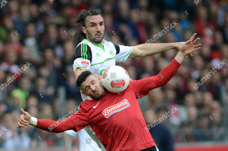 Wolfsburg's Sotirios Kyrgiakos (top) Vies For the Ball with Freiburg's Daniel Caligiuri During the Bundesliga Soccer Match Between Sc Freiburg and Vfl Wolfsburg at Mage Solar Stadium in Freiburg Germany 09 March 2013 (attention: Embargo Conditions! the Dfl Permits the Further Utilisation of Up to 15 Pictures Only (no Sequntial Pictures Or Video-similar Series of Pictures Allowed) Via the Internet and Online Media During the Match (including Halftime) Taken From Inside the Stadium And/or Prior to the Start of the Match the Dfl Permits the Unrestricted Transmission of Digitised Recordings During the Match Exclusively For Internal Editorial Processing Only (e G Via Picture Picture Databases) ) Germany Freiburg