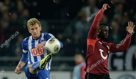 Hannover's Didier Ya Konan (r) and Hertha's Fabian Lustenberger Fight For the Ball During the German Bundesliga Soccer Match Between Hannover 96 and Hertha Bsc at the Hdi-arena in Hanover Germany 04 October 2013 Germany Hannover