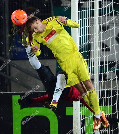 Hanover's Didier Ya Konan (l) and Arseni Logashov of Makhachkala Vie For the Ball During the Uefa Europa League Round of 32 Second Leg Soccer Match Between Hanover 96 and Fc Anzhi Makhachkala at Hannover Arena in Hanover Germany 21 February 2013 Germany Hanover