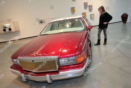 Stock Photo of A Woman Looks at the Artwork 'Pimp Juice' by Us Artist Carlos Rolon/dzine From 2013 a Mass Produced Cadillac Fleetwood Lowrider at Museum Marta in Herford Germany 13 February 2014 the Exhibition 'Booster' is About Sounds Noises and Music and It Runs From 15 February to 01 June Germany Herford