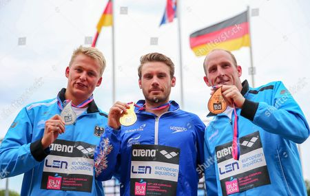 Stock Photo of Britan's Daniel Fogg (c) Poses with His Gold Medal on the Podium After Winning the Men's 5km Open Water Final During the 32nd Len European Swimming Championships 2014 at the Gruenau Course in Berlin Germany 13 August 2014 Fogg Won Ahead Second Placed Rob Muffels (l) and Third Placed Thomas Lurz (r) Both From Germany Germany Berlin