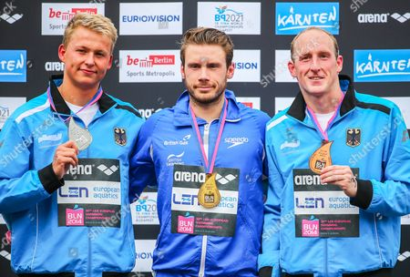 Stock Picture of Britan's Daniel Fogg (c) Poses with His Gold Medal on the Podium After Winning the Men's 5km Open Water Final During the 32nd Len European Swimming Championships 2014 at the Gruenau Course in Berlin Germany 13 August 2014 Fogg Won Ahead Second Placed Rob Muffels (l) and Third Placed Thomas Lurz (r) Both From Germany Germany Berlin