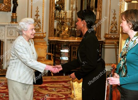 Stock Picture of Britain's Queen Elizabeth II shakes hands with Condoleezza Rice, the US Secretary of State, as Louise Miliband (right) the wife of the Foreign Secretary David Miliband looks on