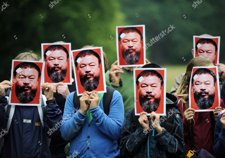 Visitors of the Contemporary Art Show Documenta (13) Hold Up Portraits of Chinese Artist Ai Weiwei in Front of Their Faces During a Protest at the Ghost Statue of Apichatpong Weerasethakul in Kassel Germany 24 August 2012 Conceptual Artist Michael Werner Initiated the Project 'Alles Fuer Aiweiwei' (lit : Everything For Ai Weiwei) Which Includes Protest Actions with Masks Such Like Those Above in Places Acoss Germany Germany Kassel