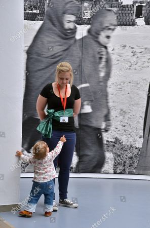 A Small Visitor of the Documenta (13) Interacts with a Documenta Employee at Museum Fridericianum in Kassel Germany 09 June 2012 a Part of a Tapestry by Polish Artist Goshka Macuga is Visible in the Background Documenta (13) Runs From 09 June to 16 September 2012 Germany Kassel