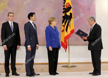 German President Joachim Gauck (r) Hands Over a Certificate of Discharge to (r-l) Germanáchancellor Angela Merkel Economics Minister Philipp Roesler and Foreign Minister Guido Westerwelle at Bellevue Palace in Berlin Germany 22 October 2013 the Current German Government Will Remain in Charge Until a New Coalition is Formed Germany Berlin