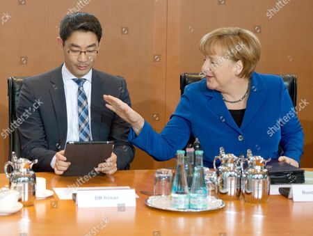 German Chancellor Angela Merkel (r) and German Economy Minister Philipp Roesler Talk Before the Start of a Cabinet Meeting in Berlin ágermany 20 November 2013 Germany Berlin