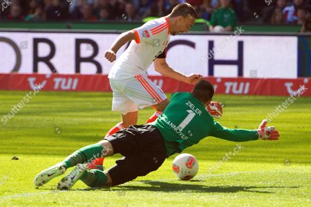 Munich's Franck Ribery (back) Vies For the Ball with Hanover's Goalkeeper Ron-robert Zieler (front) During the German Bundesliga Soccer Match Between Hanover 96 and Bayern Munich in Hanover Germany 20 April 2013 (attention: Embargo Conditions! the Dfl Permits the Further Utilisation of Up to 15 Pictures Only (no Sequential Pictures Or Video-similar Series of Pictures Allowed) Via the Internet and Online Media During the Match (including Halftime) Taken From Inside the Stadium And/or Prior to the Start of the Match the Dfl Permits the Unrestricted Transmission of Digitised Recordings During the Match Exclusively For Internal Editorial Processing Only (e G Via Picture Databases) Germany Hanover