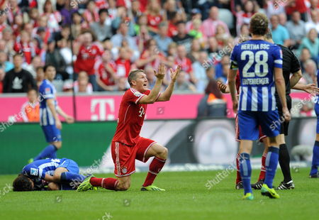 Munich's Bastian Schweinsteiger (c) Complains About a Decision of Referee Michael Weiner (hidden) During the German Bundesliga Match Between Fc Bayern Munich and Hertha Bsc at the Allianz Arena in Munich Germany 26 October 2013 (attention: Due to the Accreditation Guidelines the Dfl Only Permits the Publication and Utilisation of Up to 15 Pictures Per Match on the Internet and in Online Media During the Match ) Germany Munich