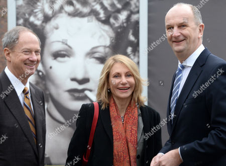 Stock Picture of Us Ambassador to Germany John Bonell Emerson (l) His Wife Kimberly Marteau Emerson and German State Governor of Brandenburg Dietmar Woidke (r) Stand in Front of a Poster of Late German Actress Marlene Dietrich at the Babelsberg Film Studios in Potsdam Germany 19áfebruary 2014 the Diplomat Visitied the Media Location During His First Courtesy Call in Brandenburg the Ambassador Informed Himself About Us Film Productions Which Were Realized in Babelsberg Germany Potsdam