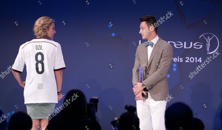 German National Soccer Player Mesut Oezil (r) Stands on Stage Looking at German Presenter Kathi Worndl (l) After Receiving the Prize For Charity at the 10th Laureus Media Award Ceremony in Berlin Germany 12 November 2014 the Laureus Media Prize is Attributed to People That Have Made an Impact to the World of Sport Germany Berlin