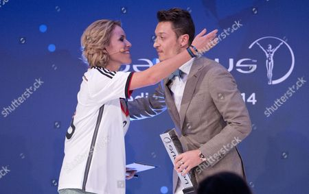 Stock Image of German National Soccer Player Mesut Oezil (r) Receives the Prize For Charity by German Presenter Kathi Worndl at the 10th Laureus Media Award Ceremony in Berlin Germany 12 November 2014 the Laureus Media Prize is Attributed to People That Have Made an Impact to the World of Sport Germany Berlin