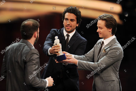 Swiss Filmmaker Baran Bo Odar (l) Receives the Best Director Award For His Movie 'Who Am i - Kein System Ist Sicher' From Actors Elyas M'barek (c) and Tom Schilling (r) During the Bavarian Film Awards Ceremony at the Prinzregententheater in Munich Germany 16 January 2015 Germany Munich