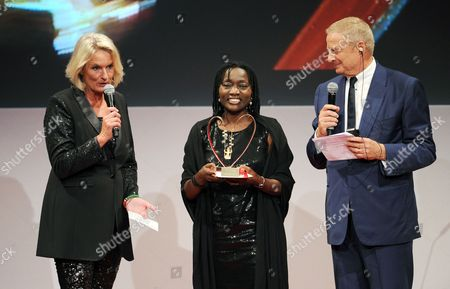 Kenyan Sociologist Auma Obama (c) the Half-sister of the Us President Smiles After Receiving the Charity Prize Prix Courage From Mona Lisa Managing Editor Sibylle Bassler (l) and Clarins Ceo Christian Courtin-clarins (r) During the Award Ceremony at the Residence of the 'Allerheiligen-hofkirch' in Munich Germany 15 October 2014 the Award Initiated by Zdf Tv Show 'Ml Mona Lisa' and the Cosmetics Company Clarins Honors Women who Have Shown an Extraordinary Commitment to Children and Youths Since 2004 Obama is Honored For the Work of Her Foundation 'Sauti Kuu' (strong Voices) Germany Munich