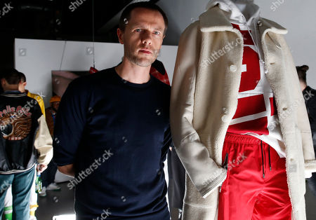 Designer Tim Coppens poses for a photograph near clothing from his capsule collection at Men's Fashion Week, in New York
