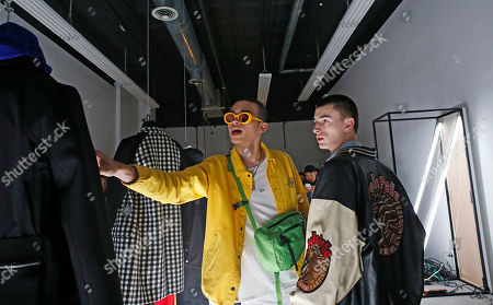 Two men discuss clothing displayed at Tim Coppens' capsule collection during Men's Fashion Week, in New York