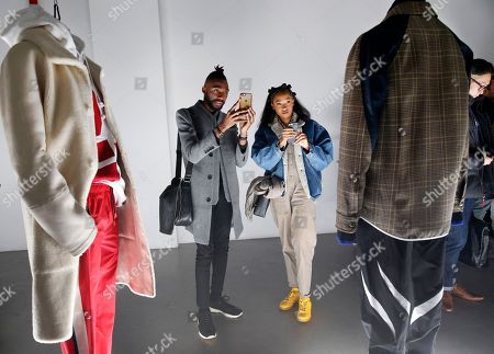 Two attendees snap cell phone photographs of the clothing during the presentation of Tim Coppens' capsule collection and book launch during Men's Fashion Week, in New York