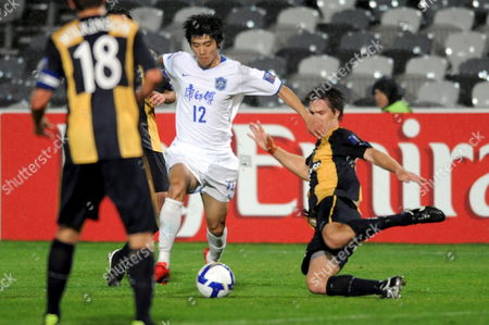 Tian Yuan (c) of the Chinese Team Tianjin Teda Faces a Tackle by the Central Coast Mariners During Their Afc Champions League Match in Gosford Australia 19 May 2009 Tianjin Won the Match 1-0 Australia Gosford
