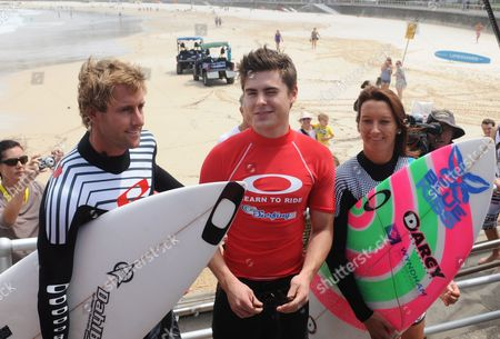 American Actor Zac Efron (c) with Pro Surfers Tom Whitaker (l) and Layne Beachley (r) on Bondi Beach Sydney Australia on 16 February 2010 Zac Efron was Taking Part in the Oakley Learn to Surf Program to Raise Money For the One Sight Foundation Australia Sydney