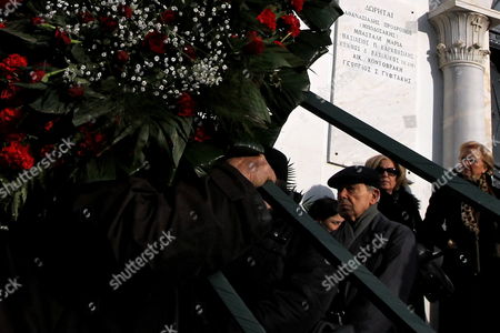 A Man Carries a Flower Wreath As Mourners Stand Next to the Church During the Funeral of Greek Director Theo Angelopoulos in Athens Greece 27 January 2012 Theo Angelopoulos Died in a Road Accident in the Early Hours on 25 January 2012 While Working on His Latest Movie Near Athens He was 76 Greece Athens