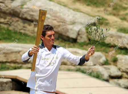 Spyros Gianniotis (c) Greek World Champion Swimmer and First Torch Bearer Runs in the Ancient Stadium of Olympia During of the Lighting Ceremony of the Olympic Flame For London Summer Olympics 2012 in Ancient Olympia Greece 10 May 2012 the Flame was Handed Over to Spyros Gianniotis Before Making a 1 800-mile Journey Through the Country Using 490 Torchbearers It Will Then Be Handed to London Organizers on May 17 in Athens' Panathenaic Stadium where the First Modern Games Were Held in 1896 the London Games Will Be Held From July 27 Until August 12 Greece Olympia