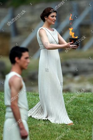 A Priestess Holds the Olympic Flame During the Lighting Ceremony of the Olympic Flame For London Summer Olympics in Ancient Olympia Greece 10 May 2012 the Flame Will Be Handed Over to the First Torchbearer Greek World Champion Swimmer Spyros Gianniotis Before Making a 1 800-mile Journey Through the Country Using 490 Torchbearers It Will Then Be Handed to London Organizers on May 17 in Athens' Panathiaic Stadium where the First Modern Games Were Held in 1896 the London Games Will Be Held From July 27 Until August 12 Greece Olympia