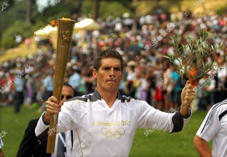 First Torchbearer Greek Swimming World Champion Spyros Gianniotis Runs with the Torch of the Olympic Flame During of the Lighting Ceremony of the Olympic Flame For London Summer Olympics 2012 in Ancient Olympia Greece 10 May 2012 the Flame was Handed Over to Spyros Gianniotis Before Making a 1 800-mile Journey Through the Country Using 490 Torchbearers It Will Then Be Handed to London Organizers on May 17 in Athens' Panathenaic Stadium where the First Modern Games Were Held in 1896 the London Games Will Be Held From July 27 Until August 12 Greece Olympia