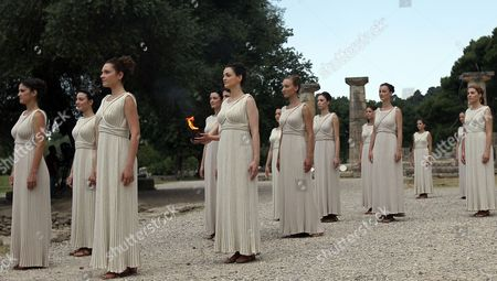Actresses Playing the Roles of Priestesses Carry a Pot with the Olympic Flame During the Lighting Ceremony of the Olympic Flame For London Summer Olympics 2012 in Front of Hera Temple in Ancient Olympia Greece 10 May 2012 the Flame Will Be Handed Over to the First Torchbearer Greek World Champion Swimmer Spyros Gianniotis Before Making a 1 800-mile Journey Through the Country Using 490 Torchbearers It Will Then Be Handed to London Organizers on May 17 in Athens' Panathiaic Stadium where the First Modern Games Were Held in 1896 the London Games Will Be Held From July 27 Until August 12 Greece Olympia