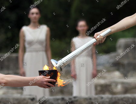 Actress Ino Menegaki (out of Frame) in the Role of the High Priestess Lights the Torch of the Olympic Flame During the Lighting Ceremony of the Olympic Flame For London Summer Olympics 2012 in Front of Hera Temple in Ancient Olympia Greece 10 May 2012 the Flame Will Be Handed Over to the First Torchbearer Greek World Champion Swimmer Spyros Gianniotis Before Making a 1 800-mile Journey Through the Country Using 490 Torchbearers It Will Then Be Handed to London Organizers on May 17 in Athens' Panathiaic Stadium where the First Modern Games Were Held in 1896 the London Games Will Be Held From July 27 Until August 12 Greece Olympia