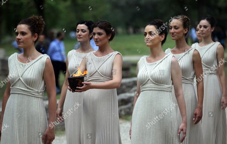 Stock Image of Actresses Playing the Roles of Priestesses Carry a Pot with the Olympic Flame During the Lighting Ceremony of the Olympic Flame For London Summer Olympics 2012 in Front of Hera Temple in Ancient Olympia Greece 10 May 2012 the Flame Will Be Handed Over to the First Torchbearer Greek World Champion Swimmer Spyros Gianniotis Before Making a 1 800-mile Journey Through the Country Using 490 Torchbearers It Will Then Be Handed to London Organizers on May 17 in Athens' Panathiaic Stadium where the First Modern Games Were Held in 1896 the London Games Will Be Held From July 27 Until August 12 Greece Olympia