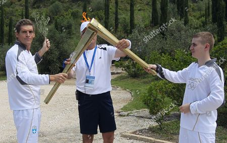 First Torchbearer Greek Wimming World Champion Spyros Gianniotis (l) Passes the Olympic Flame to the Second Torchbearer British Boxer Alexandros Loukos During the Lighting Ceremony of the Olympic Flame For London Summer Olympics 2012 in Front of Hera Temple in Ancient Olympia Greece 10 May 2012 the Flame Will Be Handed Over to the First Torchbearer Greek World Champion Swimmer Spyros Gianniotis Before Making a 1 800-mile Journey Through the Country Using 490 Torchbearers It Will Then Be Handed to London Organizers on May 17 in Athens' Panathiaic Stadium where the First Modern Games Were Held in 1896 the London Games Will Be Held From July 27 Until August 12 Greece Olympia