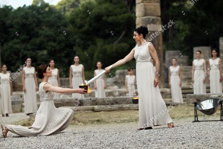 Actress Ino Menegaki (r) in the Role of the High Priestess Lights the Torch of the Olympic Flame During the Lighting Ceremony of the Olympic Flame For London Summer Olympics 2012 in Front of Hera Temple in Ancient Olympia Greece 10 May 2012 the Flame Will Be Handed Over to the First Torchbearer Greek World Champion Swimmer Spyros Gianniotis Before Making a 1 800-mile Journey Through the Country Using 490 Torchbearers It Will Then Be Handed to London Organizers on May 17 in Athens' Panathiaic Stadium where the First Modern Games Were Held in 1896 the London Games Will Be Held From July 27 Until August 12 Greece Olympia