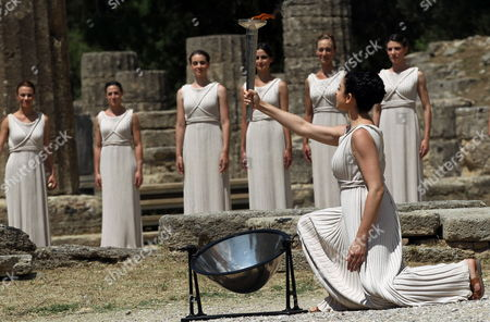 Actress Ino Menegaki in the Role of the High Priestess Lights the Torch of the Olympic Flame During the Lighting Ceremony of the Olympic Flame For London Summer Olympics 2012 in Front of Hera Temple in Ancient Olympia Greece 10 May 2012 the Flame Will Be Handed Over to the First Torchbearer Greek World Champion Swimmer Spyros Gianniotis Before Making a 1 800-mile Journey Through the Country Using 490 Torchbearers It Will Then Be Handed to London Organizers on May 17 in Athens' Panathiaic Stadium where the First Modern Games Were Held in 1896 the London Games Will Be Held From July 27 Until August 12 Greece Olympia