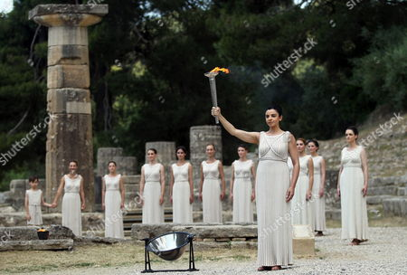 Actress Ino Menegaki in the Role of the High Priestess Raises the Torch of the Olympic Flame During the Lighting Ceremony of the Olympic Flame For London Summer Olympics 2012 in Front of Hera Temple in Ancient Olympia Greece 10 May 2012 the Flame Will Be Handed Over to the First Torchbearer Greek World Champion Swimmer Spyros Gianniotis Before Making a 1 800-mile Journey Through the Country Using 490 Torchbearers It Will Then Be Handed to London Organizers on May 17 in Athens' Panathiaic Stadium where the First Modern Games Were Held in 1896 the London Games Will Be Held From July 27 Until August 12 Greece Olympia