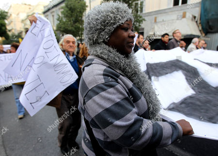 Migrants who Live in Athens and Anti-racists From Greece and Countries of Europe Demonstrate Silently Holding Banners in Central Athens on 15 December 2012 Reports State That the Silent Walk From the Greek Parliament to the Foot of the Acropolis in Protest Against a Rising Surge of Racism Anti-semitism and Neo-nazism in Greek Society and Elsewhere in Europe was Proposed by the Paris-based 'European Grassroots Antiracist Movement' (egam) Last Monday It Has the Support of Activists From 20 Countries and is Backed by Scores of Civil Rights Groups Anti-racist Movements and Some High-profile Intellectuals Such As Nobel L Aureates Dario Fo and Bernard Kouchner and French Nazi-hunter Serge Klarsfeld with Greece Acting As a Gateway Into Europe For Large Numbers of Migrants From African and Asian Countries the Dramatic Influx of Foreigners Has Helped to Whip Up Anti-migrant Sentiment Among Ordinary Greeks and Catapulted Previously Marginal Far-right Extremist Groups Such As Golden Dawn Notorious For Their Attacks on Migrants to the Forefront of the Political Scene Greece Athens