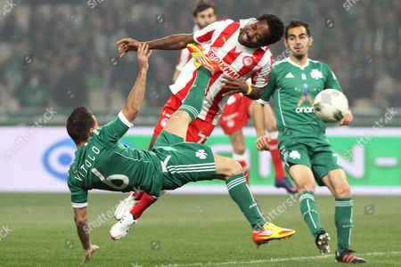 Jean Makoun (c) of Olympiacos Piraeus Vies For the Ball with Victor Vitolo (l) of Panathinaikos Athens During Their Greek Super League Soccer Match in Athens Greece 18 March 2012 Greece Athens
