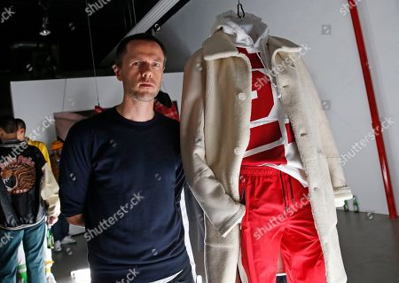 Designer Tim Coppens poses for a photograph near an outfit from his capsule collection during his show and book launch at Men's Fashion Week, in New York