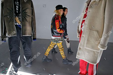 Stock Image of A couple walk through clothing displayed at the Tim Coppens capsule collection and book launch during Men's Fashion Week, in New York