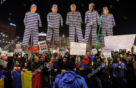 """Stock Photo of Demonstrators carry puppets depicting, left to right, Justice Minister Floring Lordache, former Prime Minister Victor Ponta, head of the senate Calin Popescu Tariceanu, leader of the social democratic party Liviu Dragnea, and Prime Minister Sorin Grindeanu during a protest in Bucharest, Romania, . Romania's political crisis is deepening over a government decree that may benefit rich and powerful people convicted of corruption. Central banner reads: """"we came to steal because it is legal"""