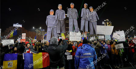 """Demonstrators carry puppets depicting, left to right, Justice Minister Floring Lordache, former Prime Minister Victor Ponta, head of the senate Calin Popescu Tariceanu, leader of the social democratic party Liviu Dragnea, and Prime Minister Sorin Grindeanu during a protest in Bucharest, Romania, . Romania's political crisis is deepening over a government decree that may benefit rich and powerful people convicted of corruption. Central banner reads: """"we came to steal because it is legal"""