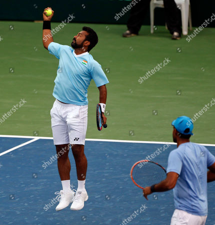 India's Leander Paes catches the ball as it bounces back from the net, with compatriot Vishnu Vardhan standing beside him during their match against New Zealand's Artem Sitak and Michael Venus in their Davis Cup tennis Asia/Oceania Group I tie in Pune, India