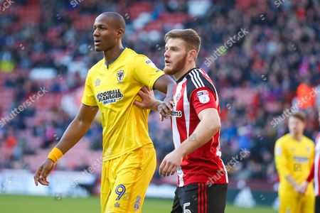 AFC Wimbledon forward Tom Elliott (9) picked up by Sheffield United defender Jack O'Connell (5)  during the EFL Sky Bet League 1 match between Sheffield Utd and AFC Wimbledon at Bramall Lane, Sheffield