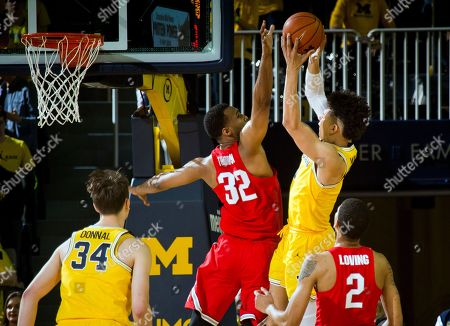 Trevor Thompson, D.J. Wilson Ohio State center Trevor Thompson (32) defends Michigan forward D.J. Wilson, top right, in the first half of an NCAA college basketball game at Crisler Center in Ann Arbor, Mich