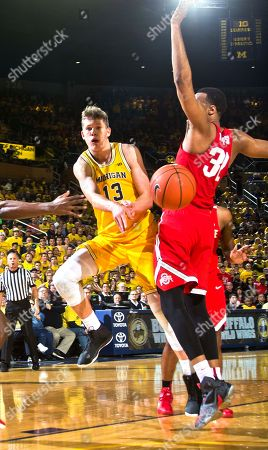 Moritz Wagner, Trevor Thompson Michigan forward Moritz Wagner (13), of Germany, passes the ball by Ohio State center Trevor Thompson (32) in the second half of an NCAA college basketball game at Crisler Center in Ann Arbor, Mich., . Ohio State won 70-66