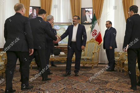 Secretary of Iran's Supreme National Security Council Ali Shamkhani, center, welcomes the Russian delegation at the start of his meeting with Russia's special envoy on Syria Alexander Lavrentiev, at his office in Tehran, Iran