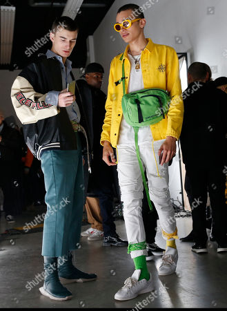 Stock Picture of Two fashionably attired men attend the Tim Coppens capsule collection show during Men's Fashion Week, in New York
