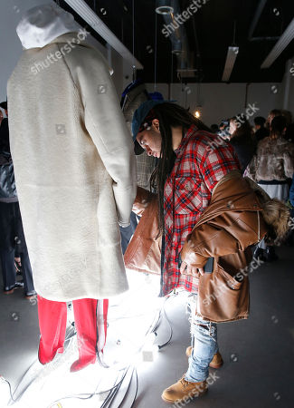 A man surveys a coat and athletic wear ensemble on display during the debut of the Tim Coppens capsule collection at Men's Fashion Week, in New York