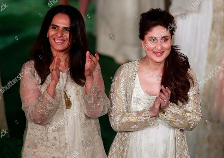 Bollywood actress Kareena Kapoor right, stands along with designer Anita Dongre at the end her grand finale during the Lakme Fashion Week in Mumbai, India