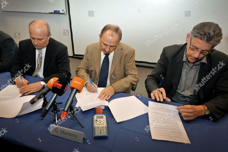 Stock Image of Ford Personnel Director Dirk Cattoir (l) Ford General Director Guy Martens (c) and Director of Ford Lommel Valere Swinnen (r) As They Sign an Agreement Form During a Press Conference of the Management and Unions of Ford Genk in Genk Belgium on 28 September 2010 Reports State That Ford Genk Announced on 27 September 2010 That They Will Keep on Producing Three Models Even After 2012 with a Production Capacity of 225 000 Vehicles Belgium Genk